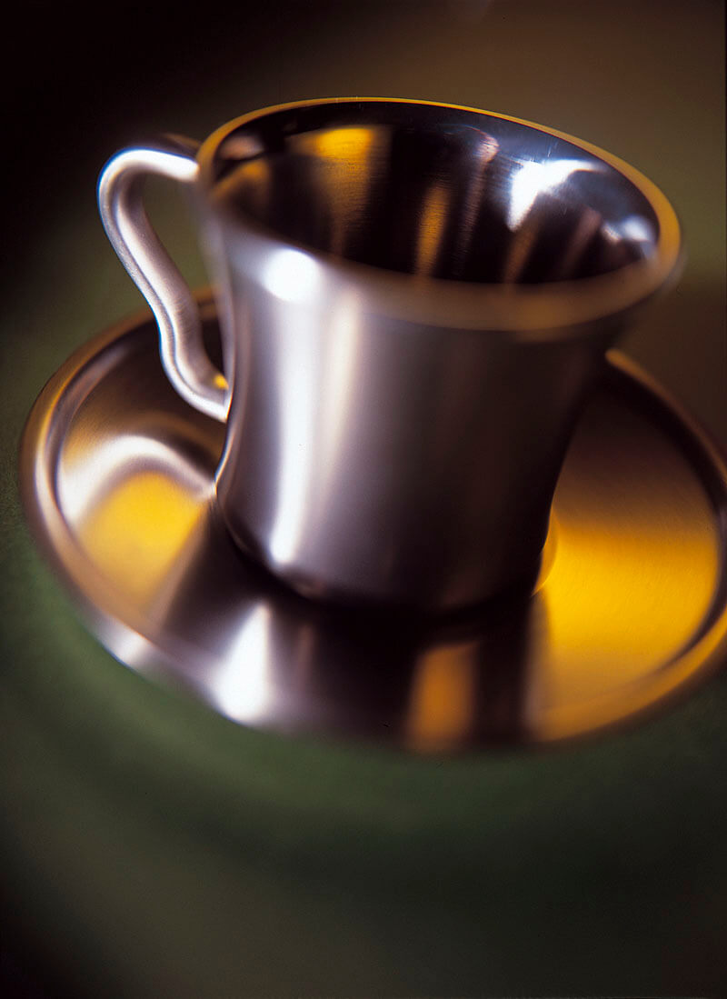 Ametal coffee cup and saucer shot using coloured yellow light